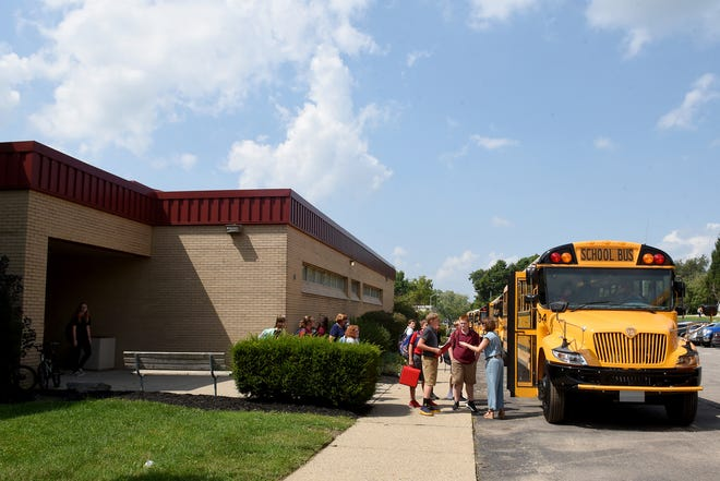 Johnstown Middle School principal Kris Almendinger helps students find their bus on the first day of school in the renovated former high school building in 2018.