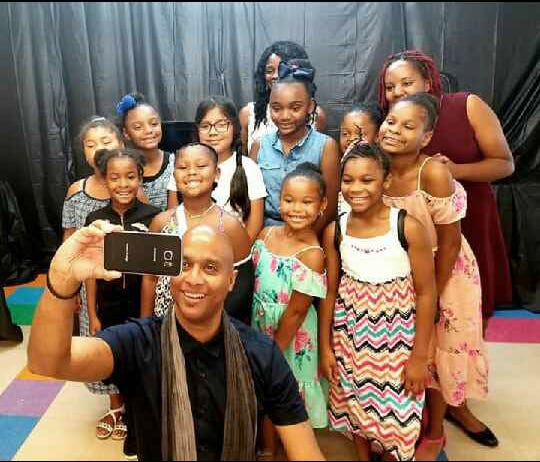 "Keith Beauchamp takes a selfie with the girls and staff of the Bella Chanel Mentoring Program of Passaic.  Beauchamp produces, directs and hosts the ""Injustice Files"" on the Discovery Channel.  His film, ""The Untold Story of Emmett Till"" reopened the case in 2004.  Keith spoke to the girls, parents and members of the community about the Till case and the history of the civil rights movement.  Passaic Mayor Hector Lora also spoke at the event.  The Bella Chanel Mentoring Program provides educational, cultural and recreational activities for local girls ages 7-14 on Saturdays."