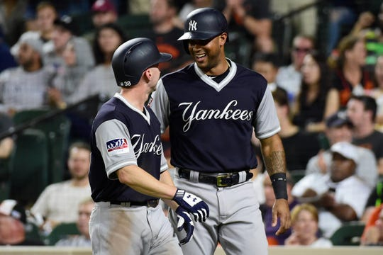 New York Yankees left fielder Shane Robinson (38) celebrates with New York Yankees designated hitter Aaron Hicks (31) after scoring on  third baseman Miguel Andujar (not pictured) two-run double.