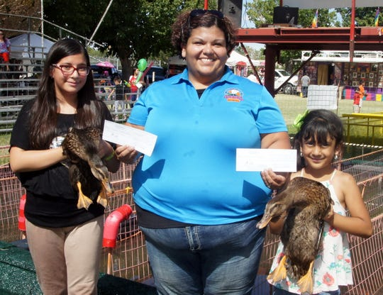Great American Duck Race Board President Joanna Costilla presented two checks for $1,380 each to the 39th annual Great American Duck Race champions, Aintza Castaneda left, and Kyanna Munoz, at right.