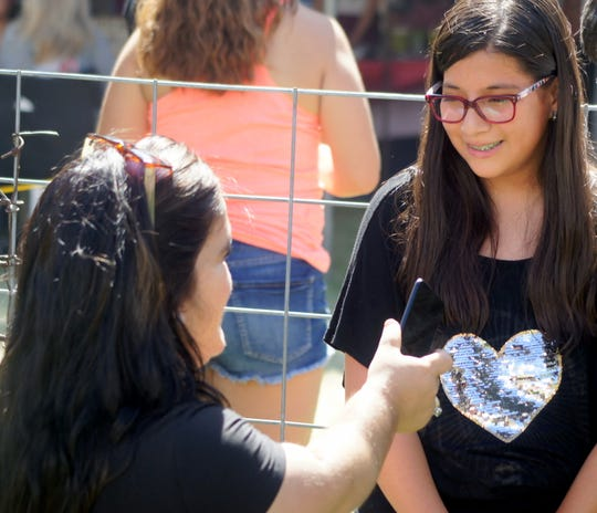 Aintza Castaneda give a winner's interview with Deming Headlight reporter Xchelzin Pena following her victory on the wet track at the 39th annual Great American Duck Race in Deming, NM.