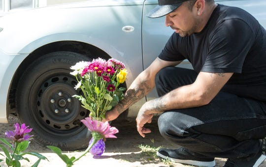 Chris Hernandez places flowers on Monday, August 27, 2018, near the vehicle of his cousin, Raymond Hernandez, 29, who died on Sunday evening after being shot near his home on Bowman Avenue.