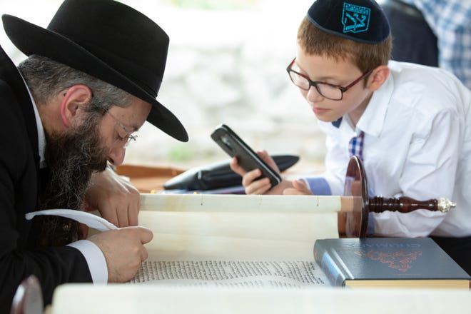 Rabbi Moshe Liberow, a scribe, works on a new Torah scroll on Sunday, Aug. 26, 2018 as Meir Schmukler, 9, looks on at the Chabad Jewish Center of Las Cruces. The synagogue raised $52,000 nearly a year ago to commission the new scroll, which was inducted on Sunday. The Torah scroll contains the five books of Moses in the original Hebrew and is read each week during prayer.