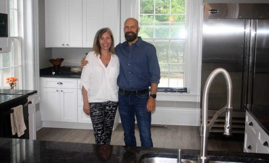 Elizabeth and Rhett Reader stand in a kitchen they recently remodeled in their  newest sober home.