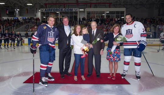 Before the first-annual Stars & Stripes Showdown, the family of Jim Johannson awaits the ceremonial puck drop along with team captains Patrick Kane (left) and Auston Matthews (34). Family members include Johannson's brother John (second from left), wife Abby (holding 2-year-old daughter Ellie), father Ken and sister Judy.