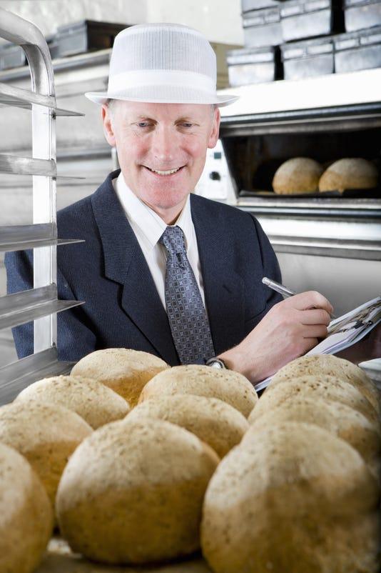 Inspector Examining Loaves Of Bread In Bakery