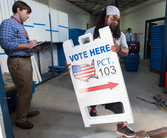 Blake Evans, from the Supervisors of Election's Office, monitors the activity as Wilmon Williams, of Coastal Moving and Storage, helps to load supplies for Tuesday's election onto a truck for delivery to local precinct polling stations in Escambia County on Monday, Aug. 27, 2018.