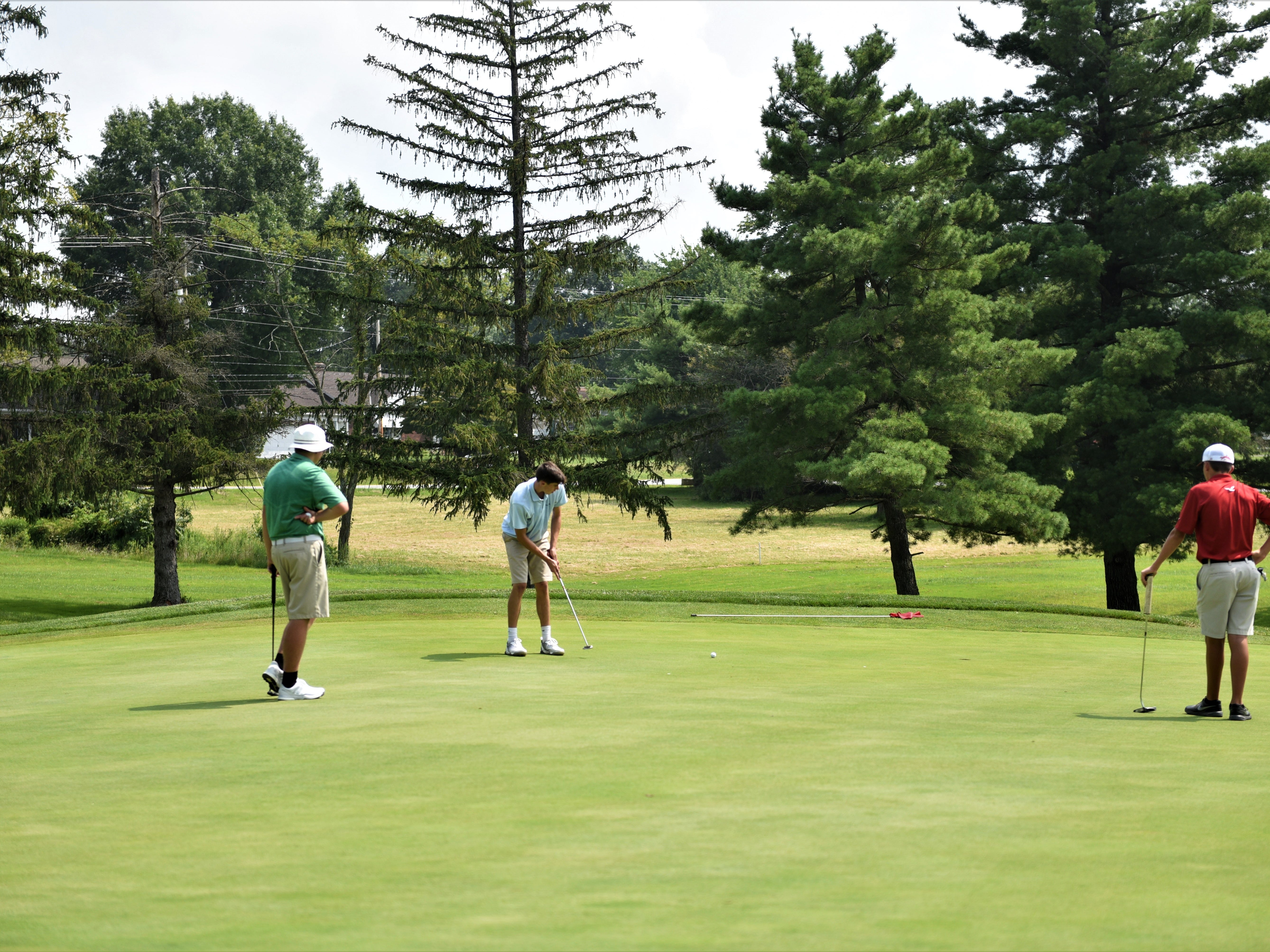 York Catholic's Russel McPaul, left and Bermudian Springs' Tucker Byers, right, wait while Delone Catholic's Corbyn Keller putts during the Division III golf match at the South Hills Golf Course on Aug. 27, 2018.
