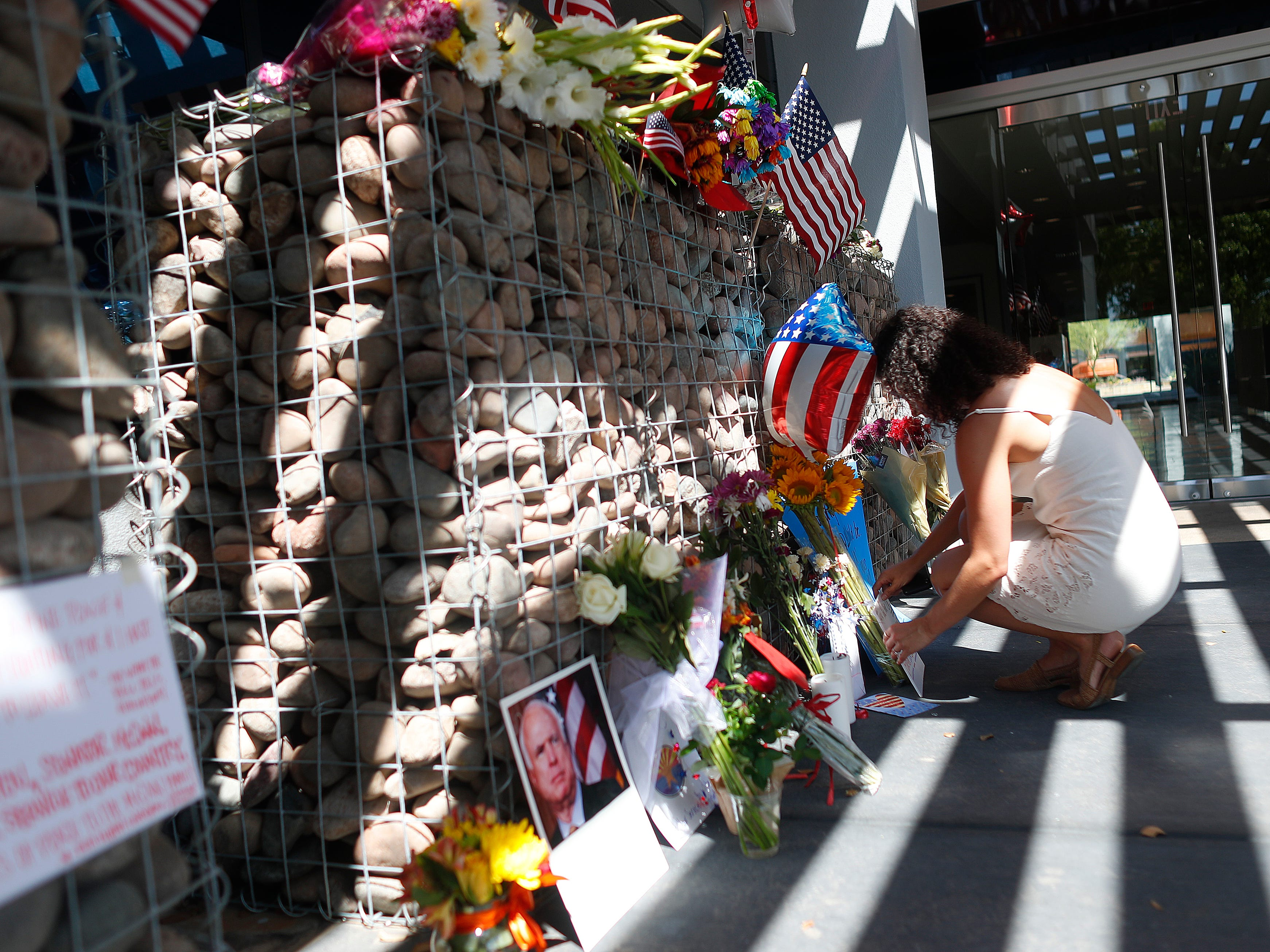 "Cass Possehl lays flowers and a note at a memorial outside Sen. John McCain's offices in Phoenix on Aug. 26, 2018. Possehl began getting into politics when she was in high school in 2008 during McCain's campaign. She worked on his last campaign and loved that his philosophy of ""values and compassion over politics."""