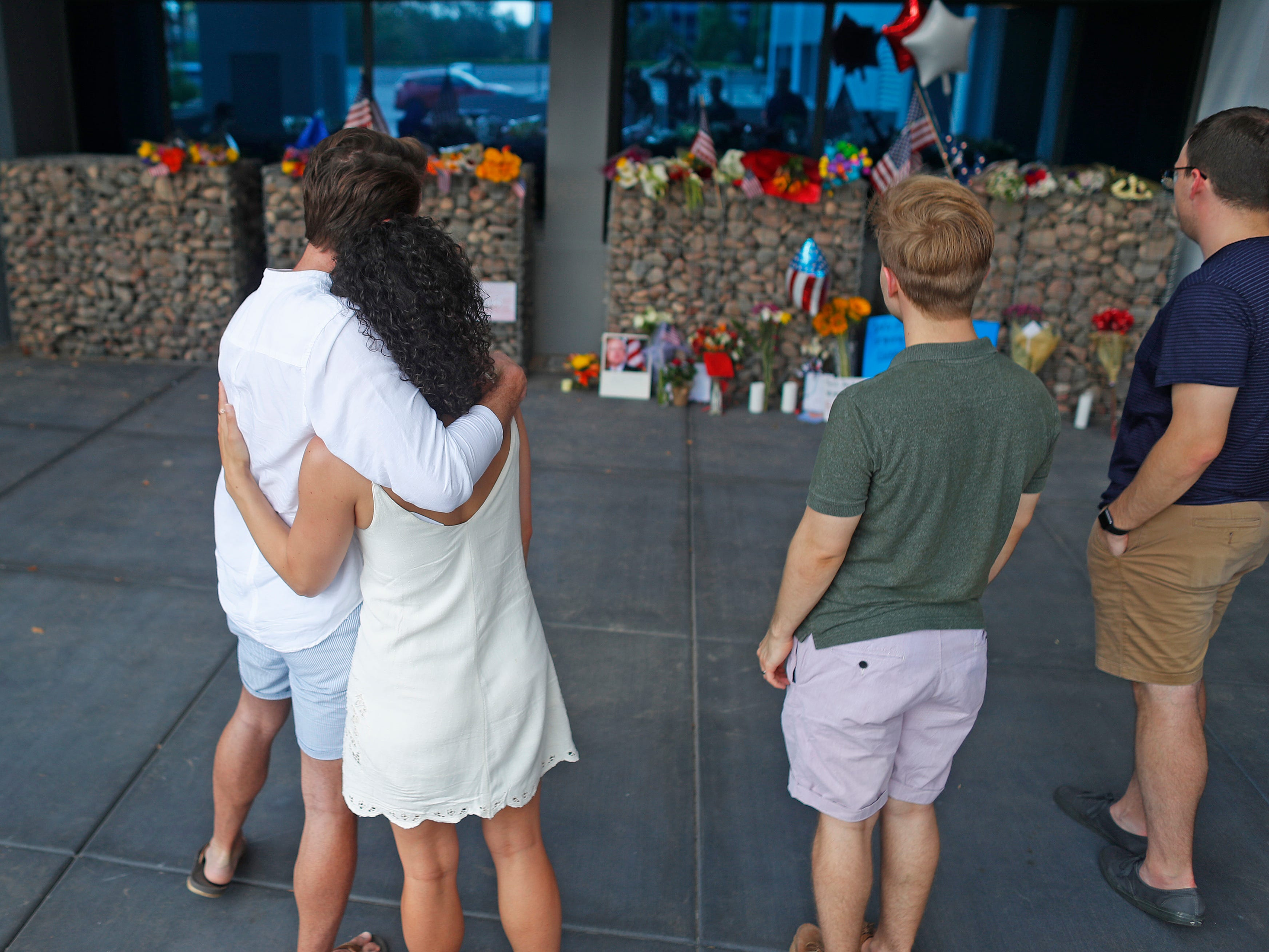Spencer Crouder hugs Cass Possehl as they look at a memorial outside Sen. John McCain's offices in Phoenix on Aug. 26, 2018.