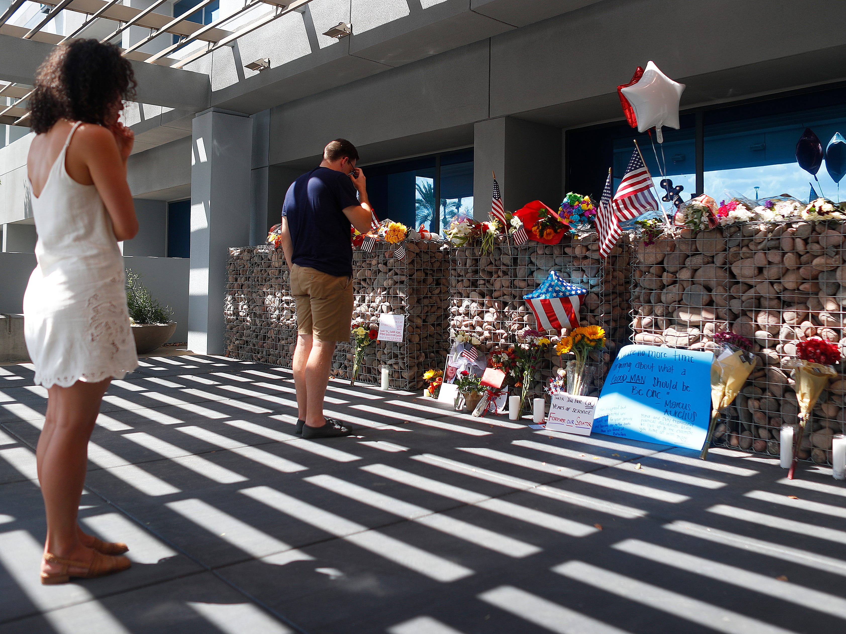 Cass Possehl watches as her friend Michael Einstein lays flowers at a memorial outside Sen. John McCain's offices in Phoenix on Aug. 26, 2018.