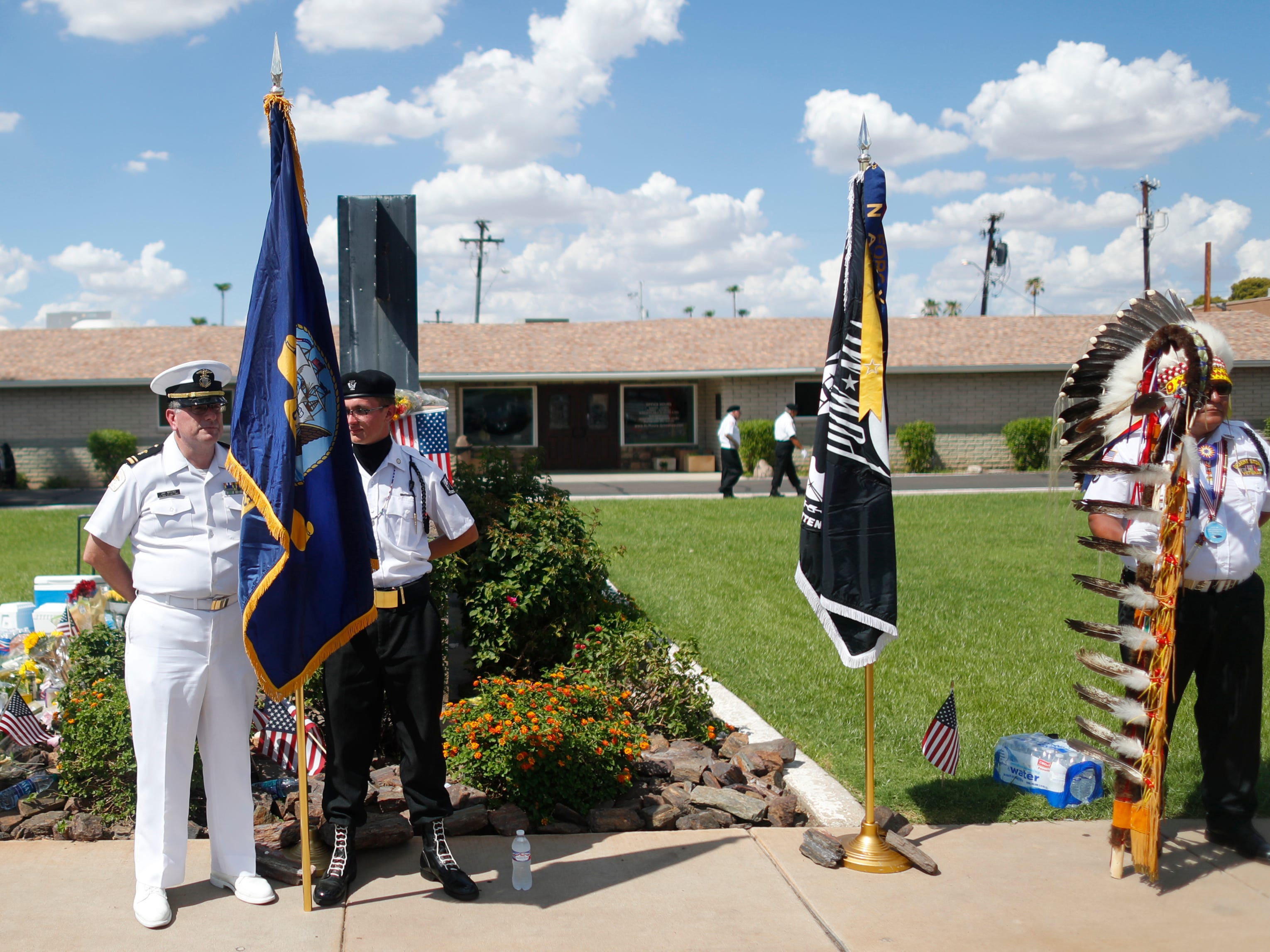 An honor guard holds its spot outside A.L. Moore-Grimshaw Mortuaries next to a memorial for Sen. John McCain in Phoenix on Aug. 26, 2018.