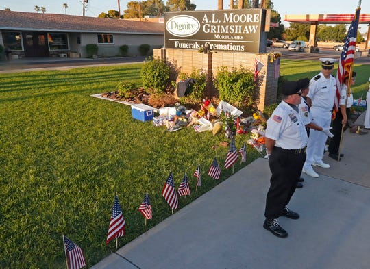 Tim McLennan, an honor guard member, arrives to stand along the line of a memorial outside A.L. Moore-Grimshaw Mortuaries in Phoenix on Aug. 26, 2018.