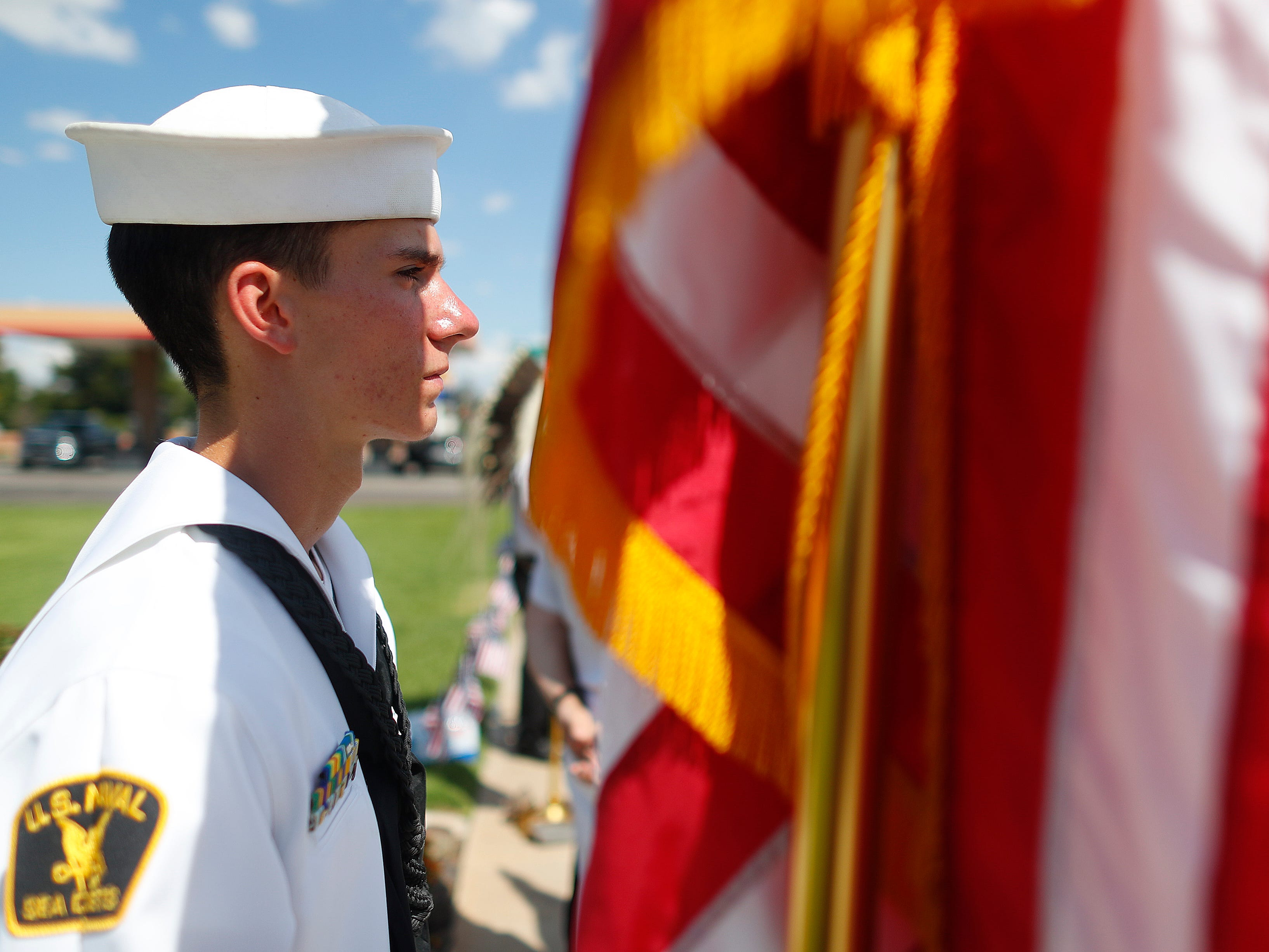 Petty Officer 3rd Class Kyle Vonnahme (USNSCC) holds an American flag in the heat as people come to honor Sen. John McCain outside A.L. Moore-Grimshaw Mortuaries in Phoenix on Aug. 26, 2018.