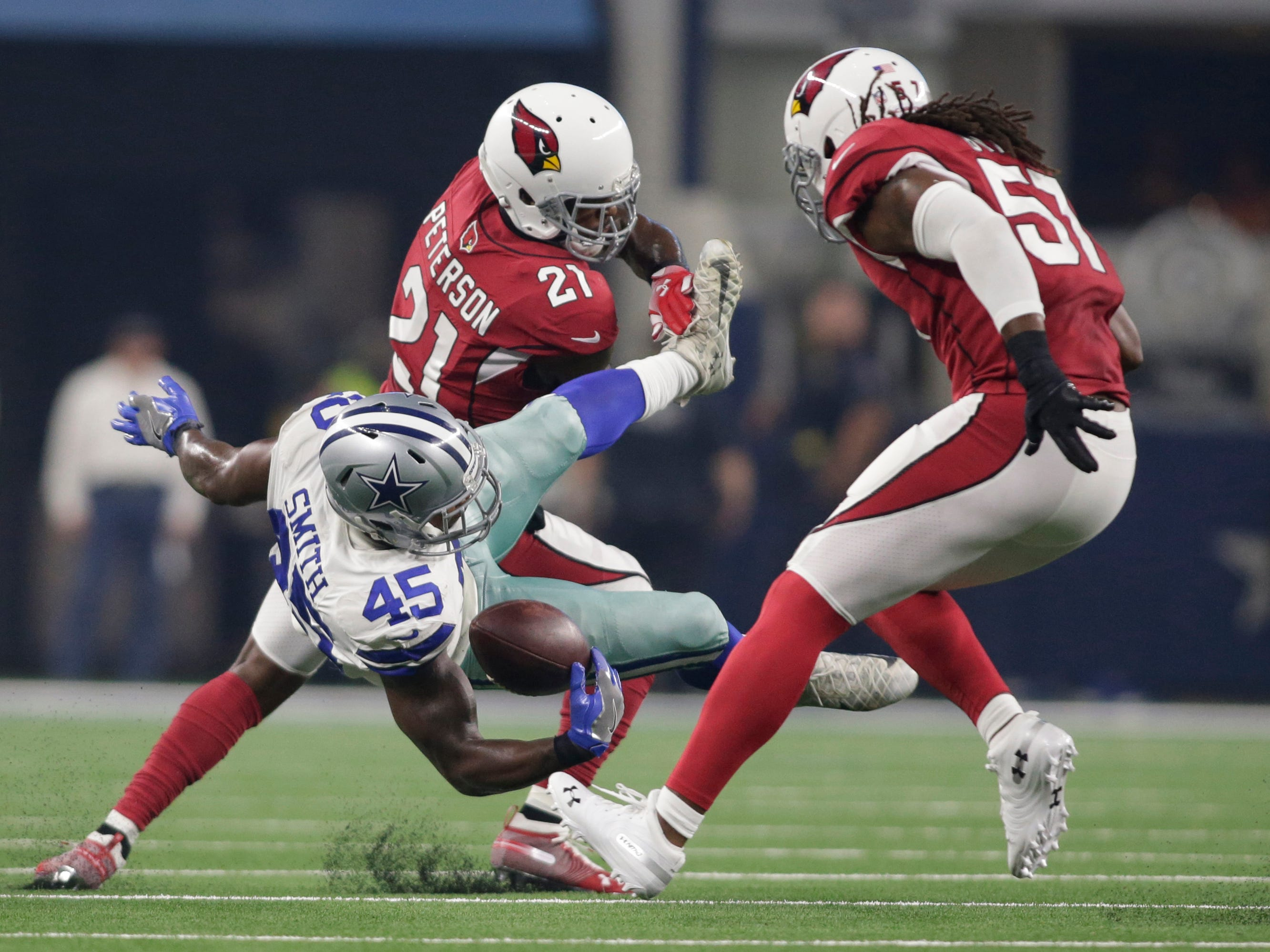 Aug 26, 2018; Arlington, TX, USA; Arizona Cardinals defensive back Patrick Peterson (21) tackles and causes a fumble by Dallas Cowboys running back Rod Smith (45) as Cardinals linebacker Josh Bynes (57) reacts during the first quarter at AT&T Stadium.