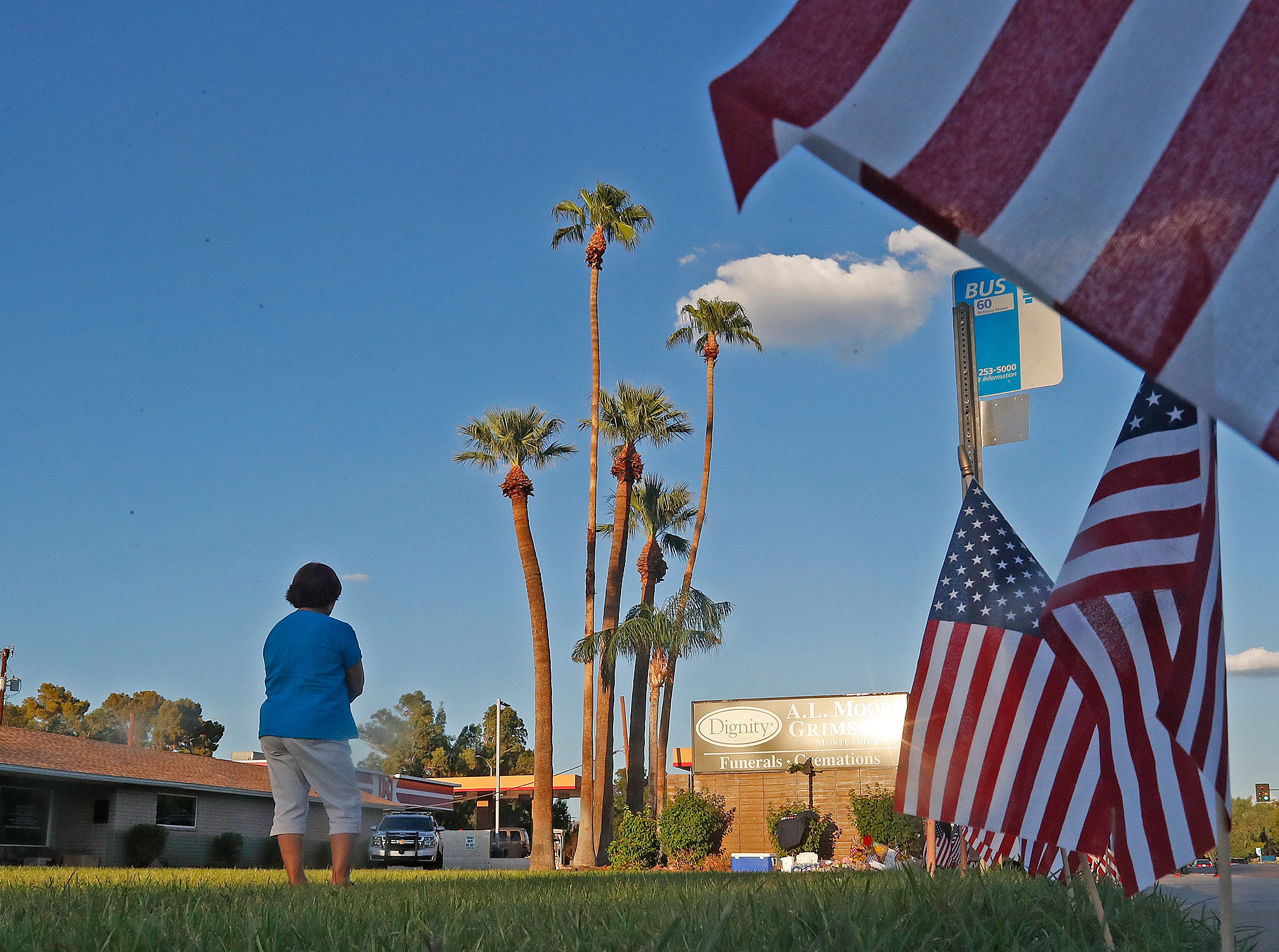 Maria Guzman looks at the growing memorial as flags line the sidewalks outside A.L. Moore-Grimshaw Mortuaries in Phoenix on Aug. 26, 2018.