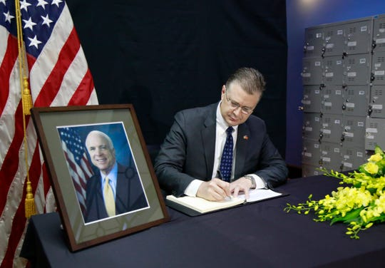 U.S. Ambassador to Vietnam Daniel Kritenbrink writes a note in a book of condolences for the late U.S. Sen. John McCain in Hanoi, Vietnam, on Aug. 27, 2018. Vietnam has been paying respect to McCain who died on Saturday.