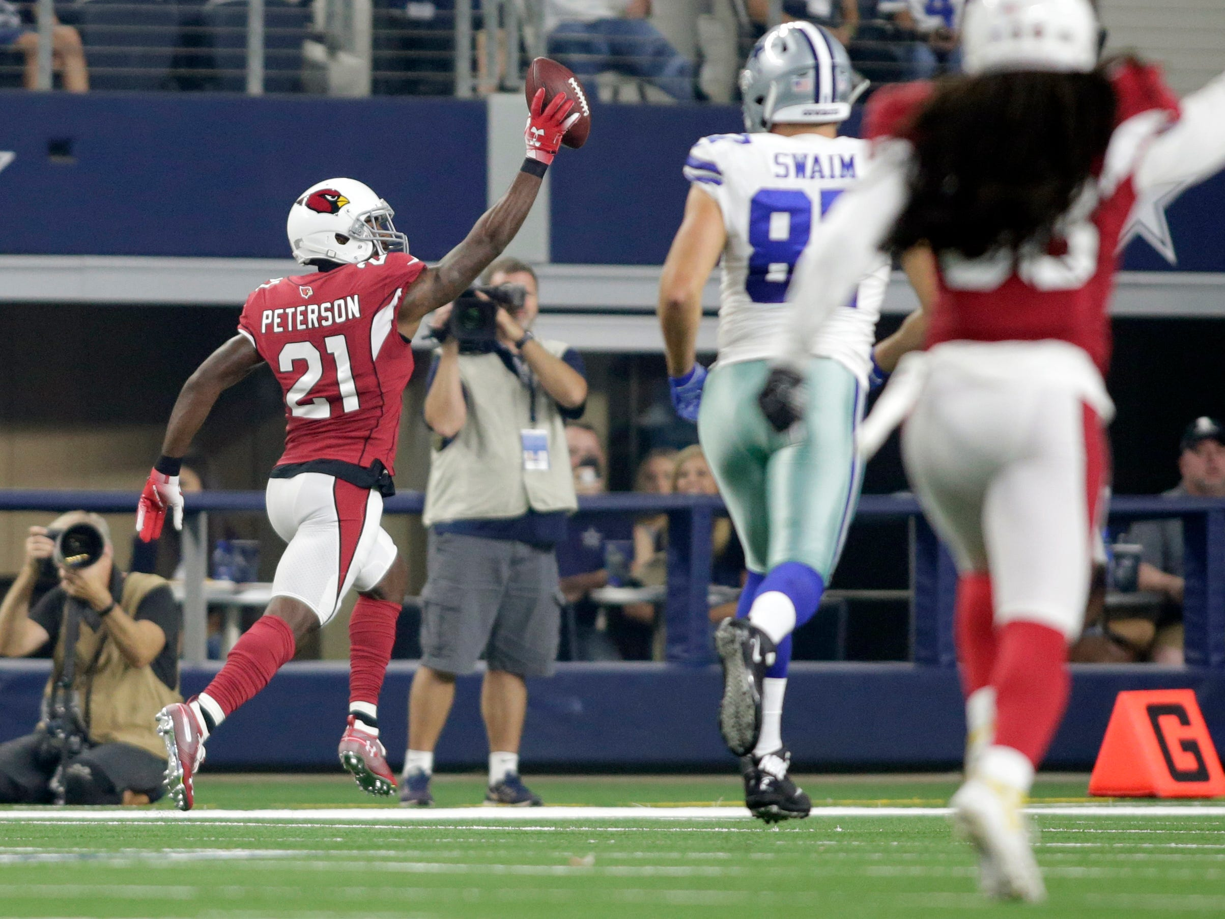 Aug 26, 2018; Arlington, TX, USA; Arizona Cardinals defensive back Patrick Peterson (21) returns a pass for a touchdown in the first quarter against the Dallas Cowboys at AT&T Stadium.