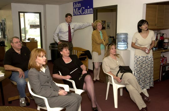 John Tyler (from left), Kirstin Tully, Babs Donaldson, Larry Pike (standing), Deb Gullett (standing), Deb Jacobus and Bettina Nava watch a TV broadcast at McCain headquarters as the senator announces the end of his campaign for president in March 2000.
