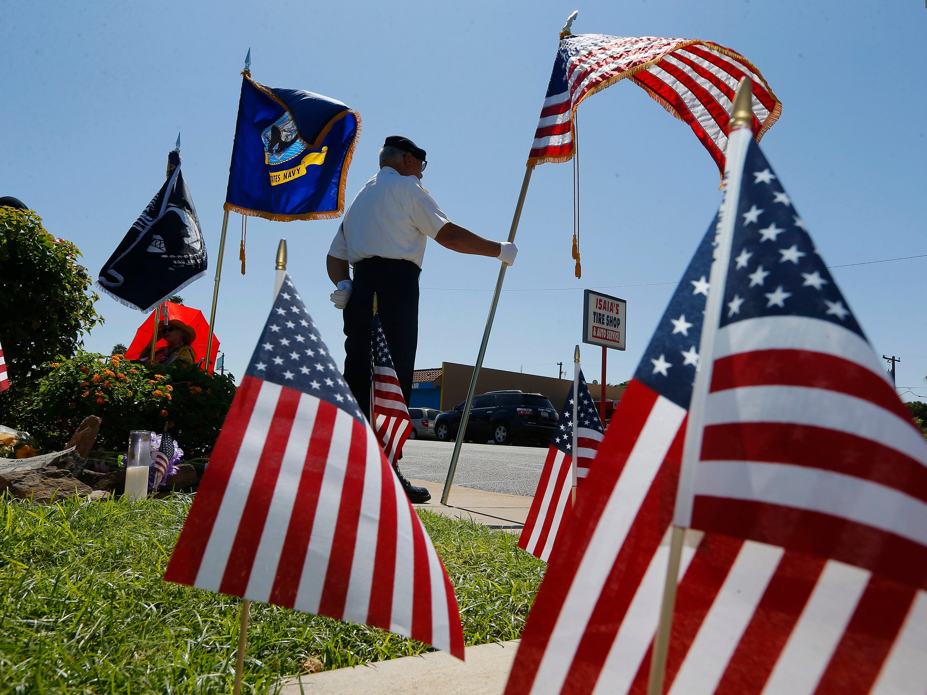 Flags frame David Carrasco, a member of the POW-MIA-KIA Honor Guard, as he stands watch in honor of the late Arizona Republican Sen. John McCain at a local mortuary where McCain is being kept Aug. 27, 2018, in Phoenix.