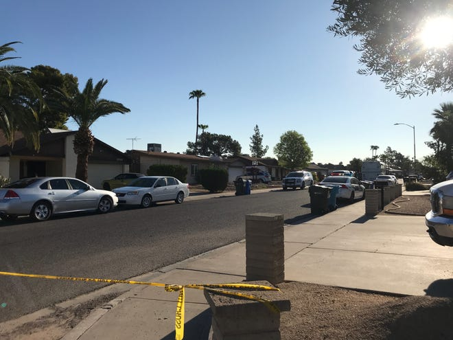 Caution tape ropes off an area of Anderson Drive where police shot a suspect in north Phoenix on August 27, 2018.