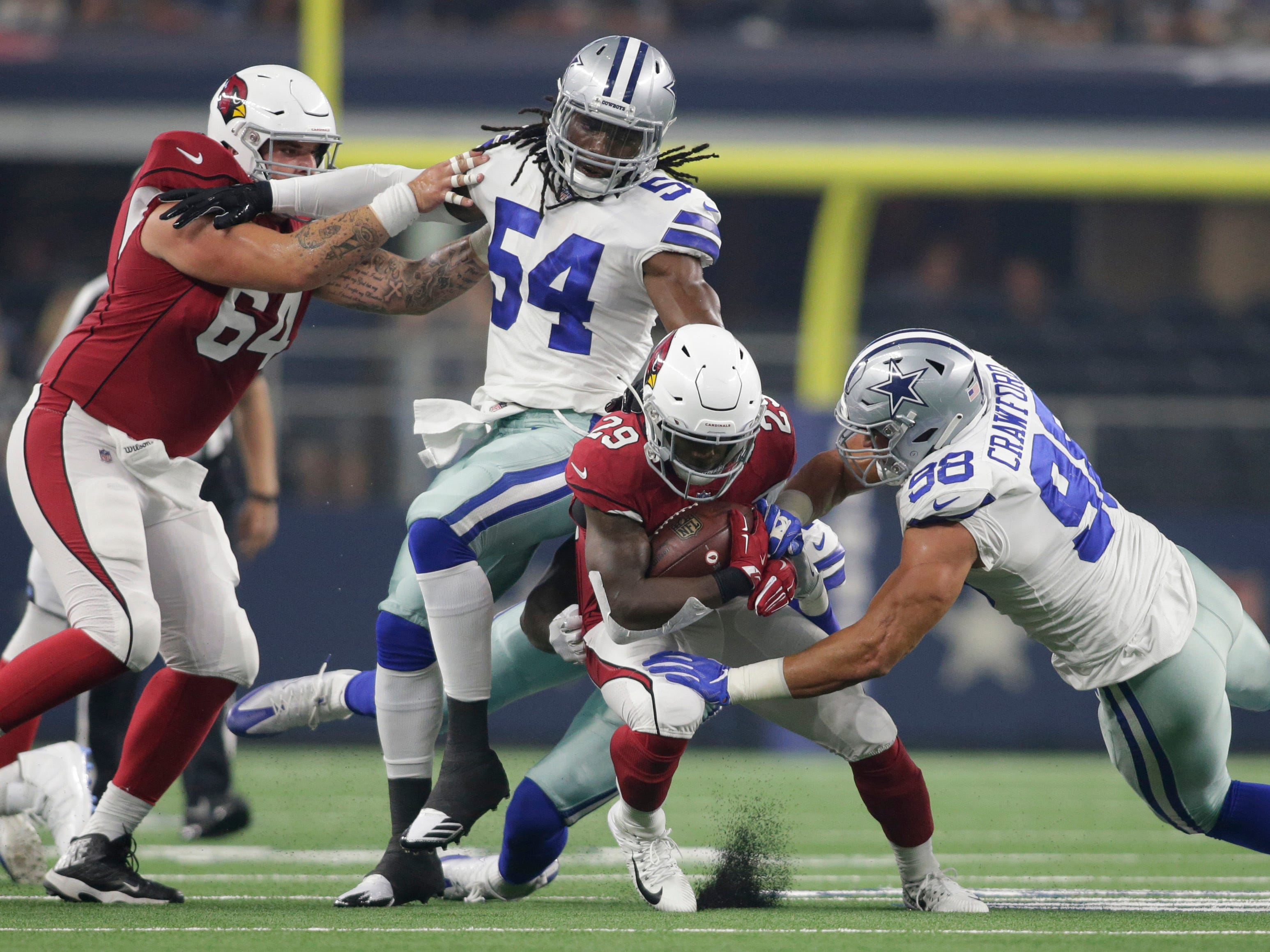 Aug 26, 2018; Arlington, TX, USA; Arizona Cardinals running back Chase Edmonds (29) is tackled by Dallas Cowboys defensive end Tyrone Crawford (98) and linebacker Jaylon Smith (54) in the first quarter at AT&T Stadium.
