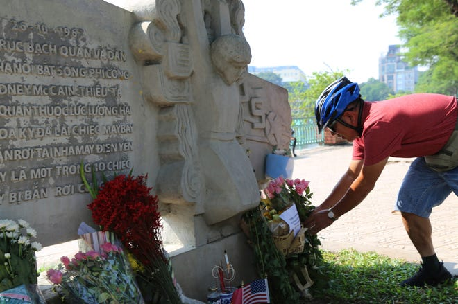 Pham Van Khanh, a 62-year-old retiree, lays flowers at the monument of Sen. John McCain in Hanoi, Vietnam on Aug. 27, 2018. The monument was erected by Vietnamese authority to mark the day when McCain's plane was shot down in 1967.