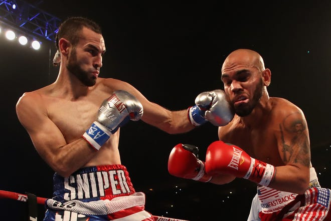 Jose Pedraza (L) of Puerto Rico throws a left on Raymundo Beltran during the WBO lightweight championship bout at Gila River Arena on Saturday in Glendale.
