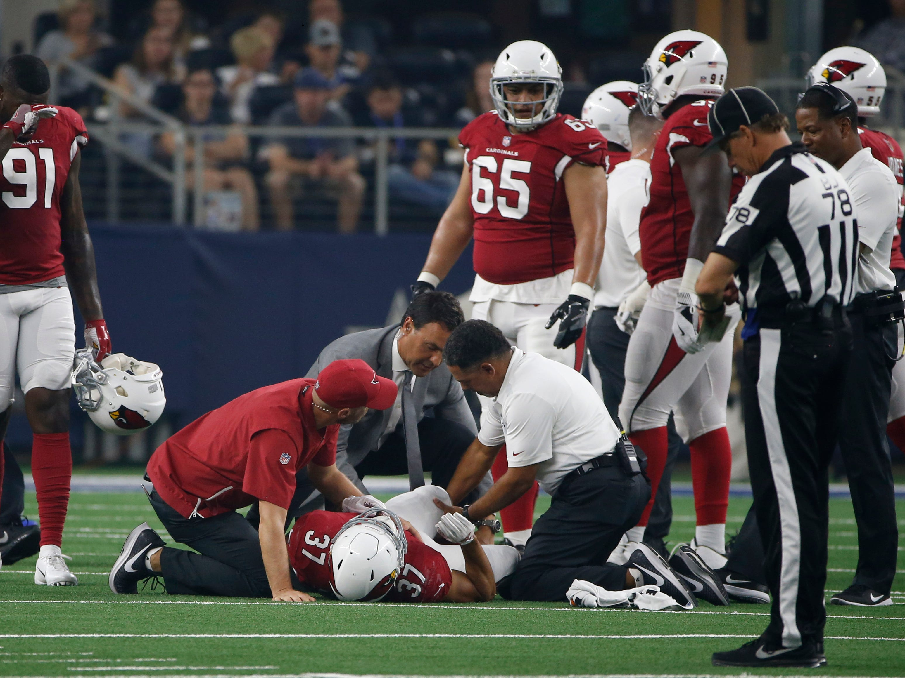 Arizona Cardinals running back D.J. Foster (37) is helped off of the field after an injury during the first half of a preseason NFL football game against the Dallas Cowboys in Arlington, Texas, Sunday, Aug. 26, 2018. (AP Photo/Ron Jenkins)