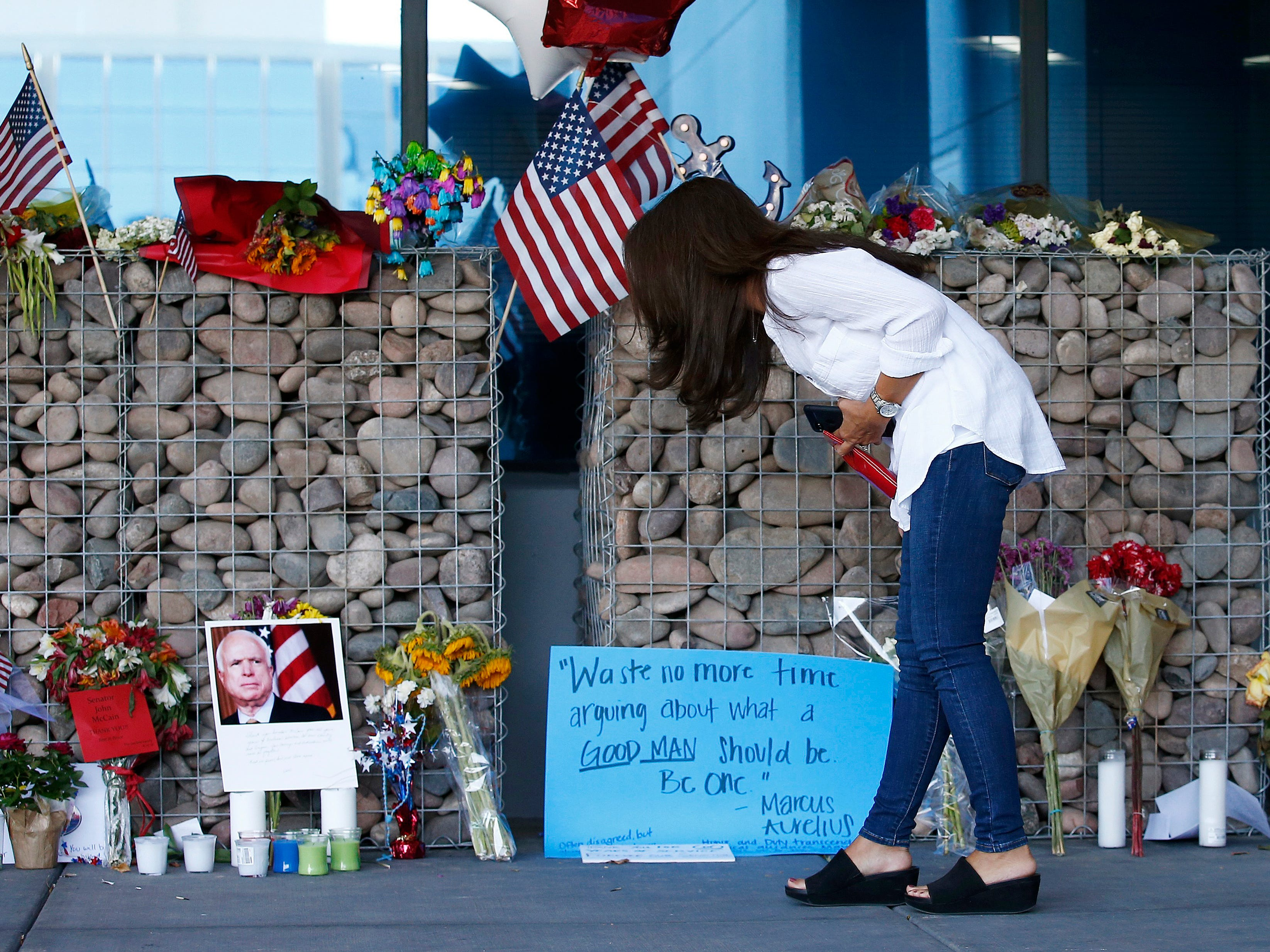 Thu-Van Cunningham, of Phoenix, reads messages left by well-wishers as she visits a makeshift memorial in honor of the late Arizona Republican Sen. John McCain at McCain's office Monday, Aug. 27, 2018, in Phoenix. McCain, the war hero who became the GOP's standard-bearer in the 2008 election, died at the age of 81, Saturday, Aug. 25, 2018, after battling brain cancer.