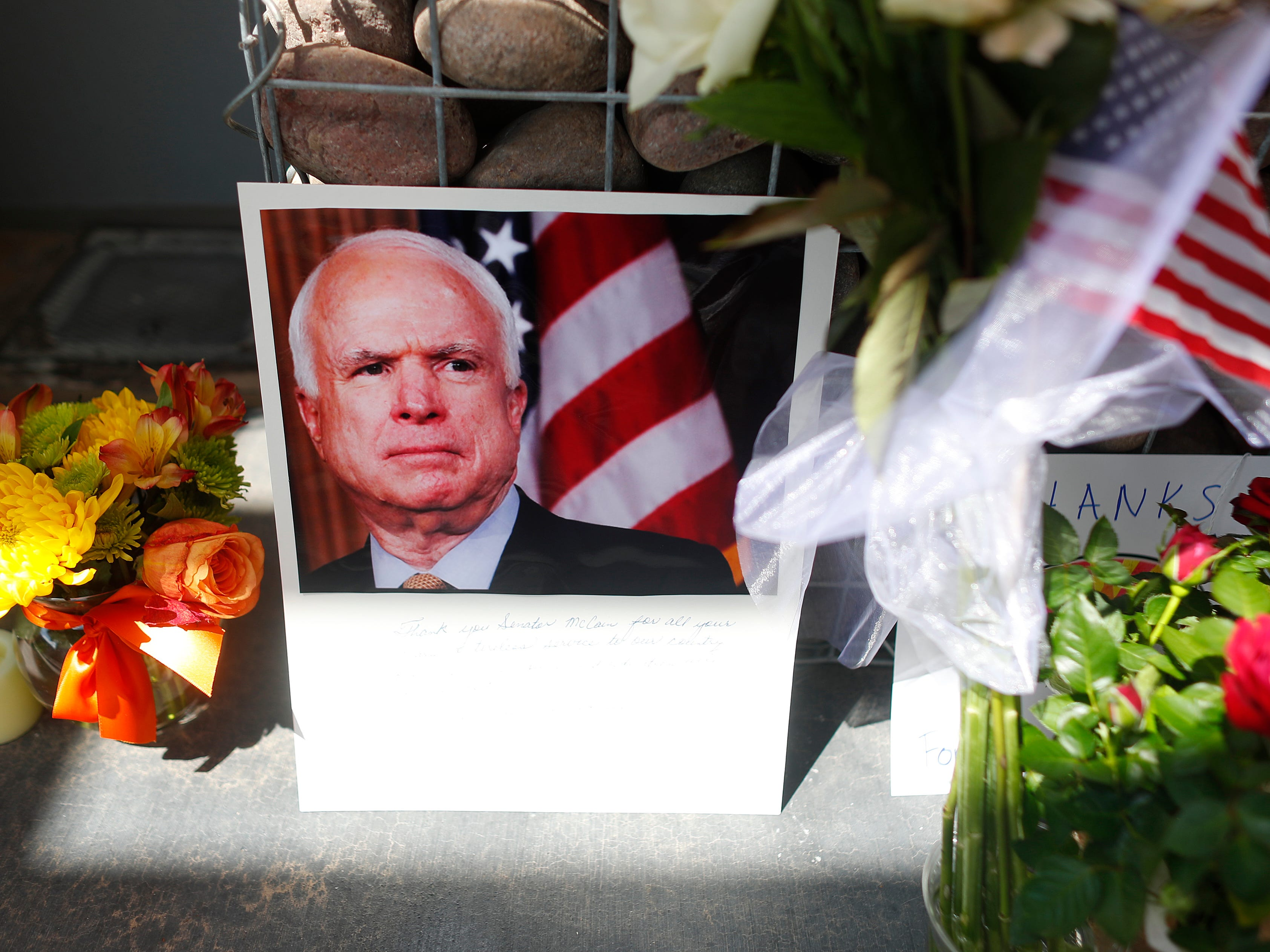 Flowers, flags and portraits of the late Sen. John McCain sit outside McCain's offices at a memorial in Phoenix on Aug. 26, 2018.