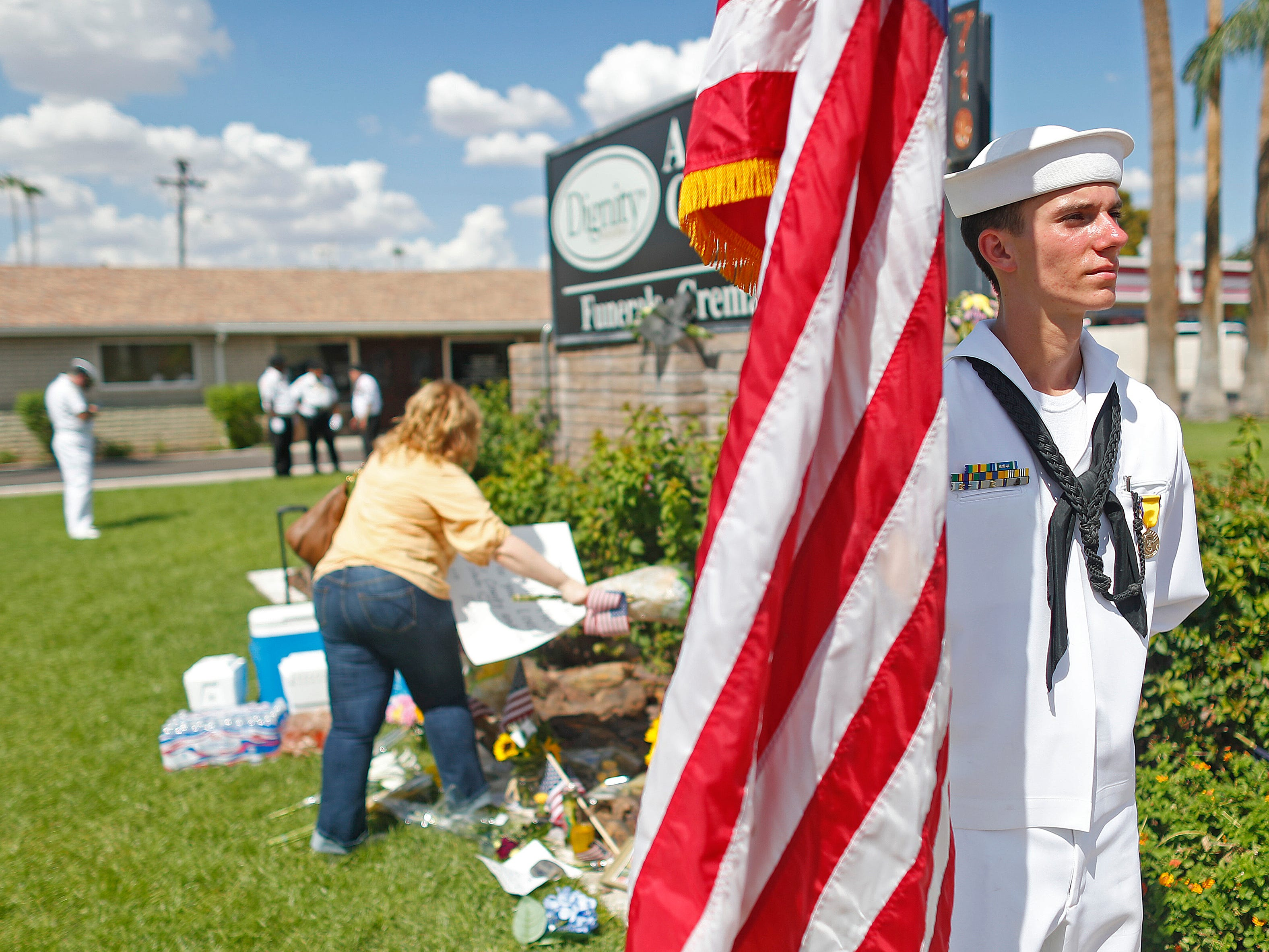 Petty officer third class Kyle Vonnahme (USNSCC) holds an American flag in the heat as people come to honor Sen. John McCain outside A.L Moore-Grimshaw Mortuaries in Phoenix, Ariz. on Aug. 26, 2018.