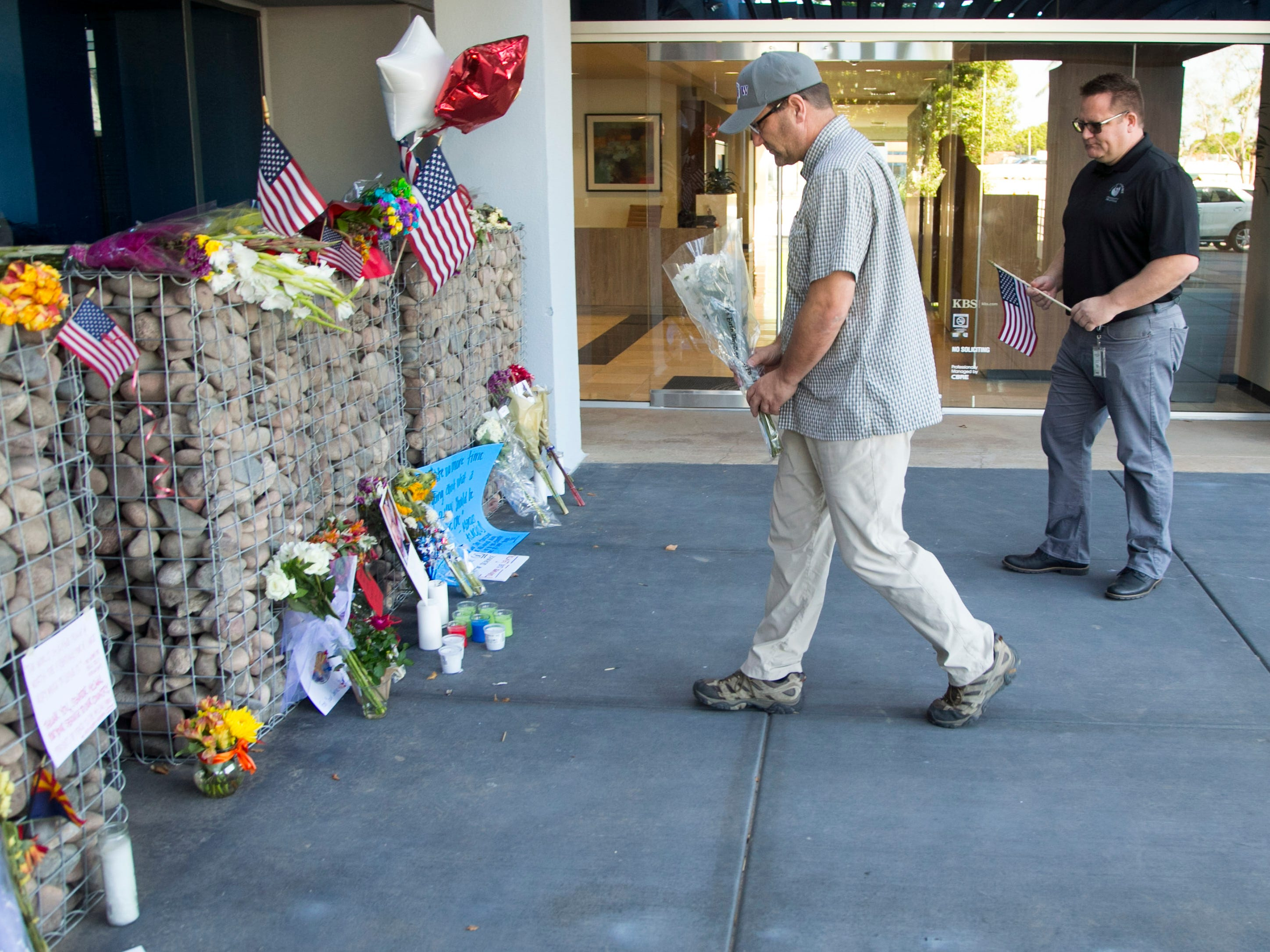 James Olsen (center) of Columbia, S.C., and his brother, Ted Olsen of Phoenix, place flowers and an American flag at a memorial for Sen. John McCain at McCain's office in Phoenix on Aug. 27, 2018.