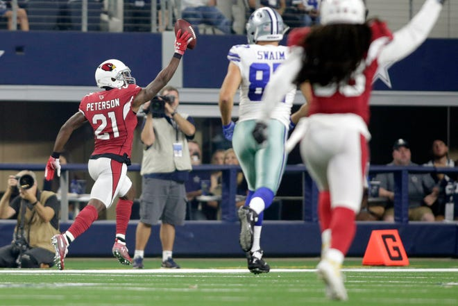 Arizona Cardinals defensive back Patrick Peterson (21) returns a pass for a touchdown in the first quarter against the Dallas Cowboys at AT&T Stadium.
