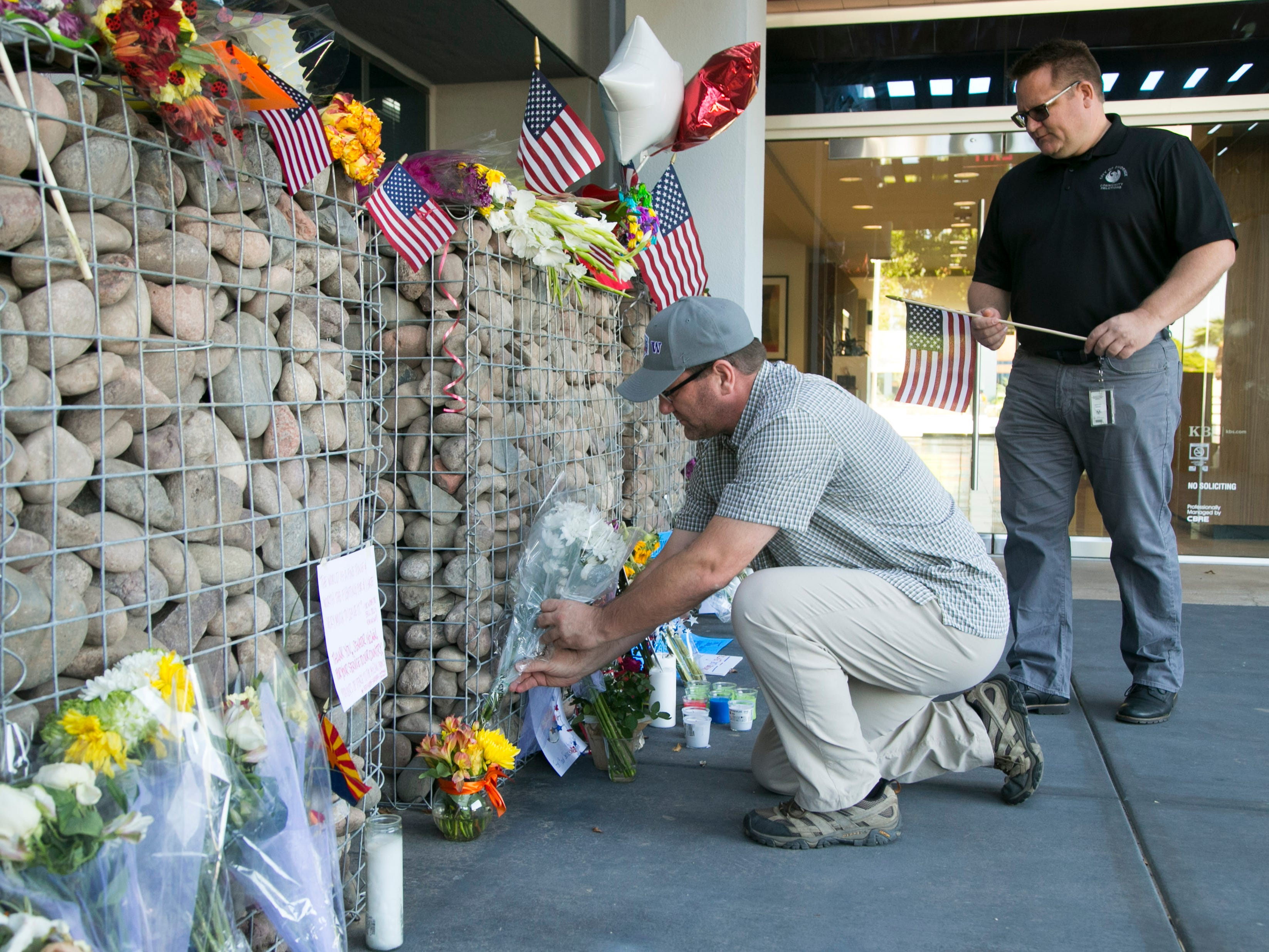 James Olsen (bottom) of Columbia, S.C., and his brother, Ted Olsen of Phoenix, place flowers and an American flag at a memorial for Sen. John McCain at McCain's office in Phoenix on Aug. 27, 2018.