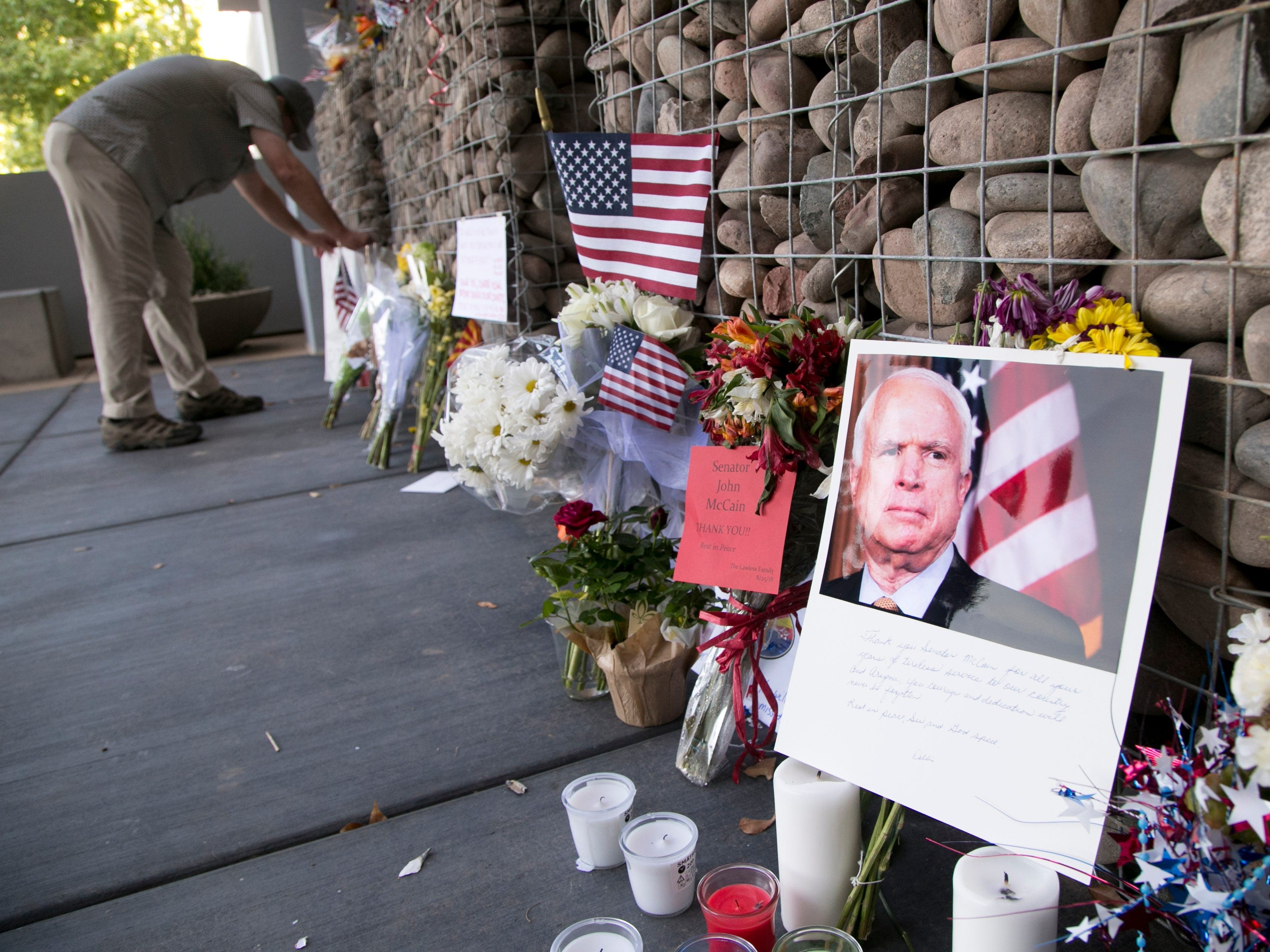James Olsen of Columbia, S.C., looks at a memorial for Sen. John McCain at McCain's office in Phoenix on Aug. 27, 2018.