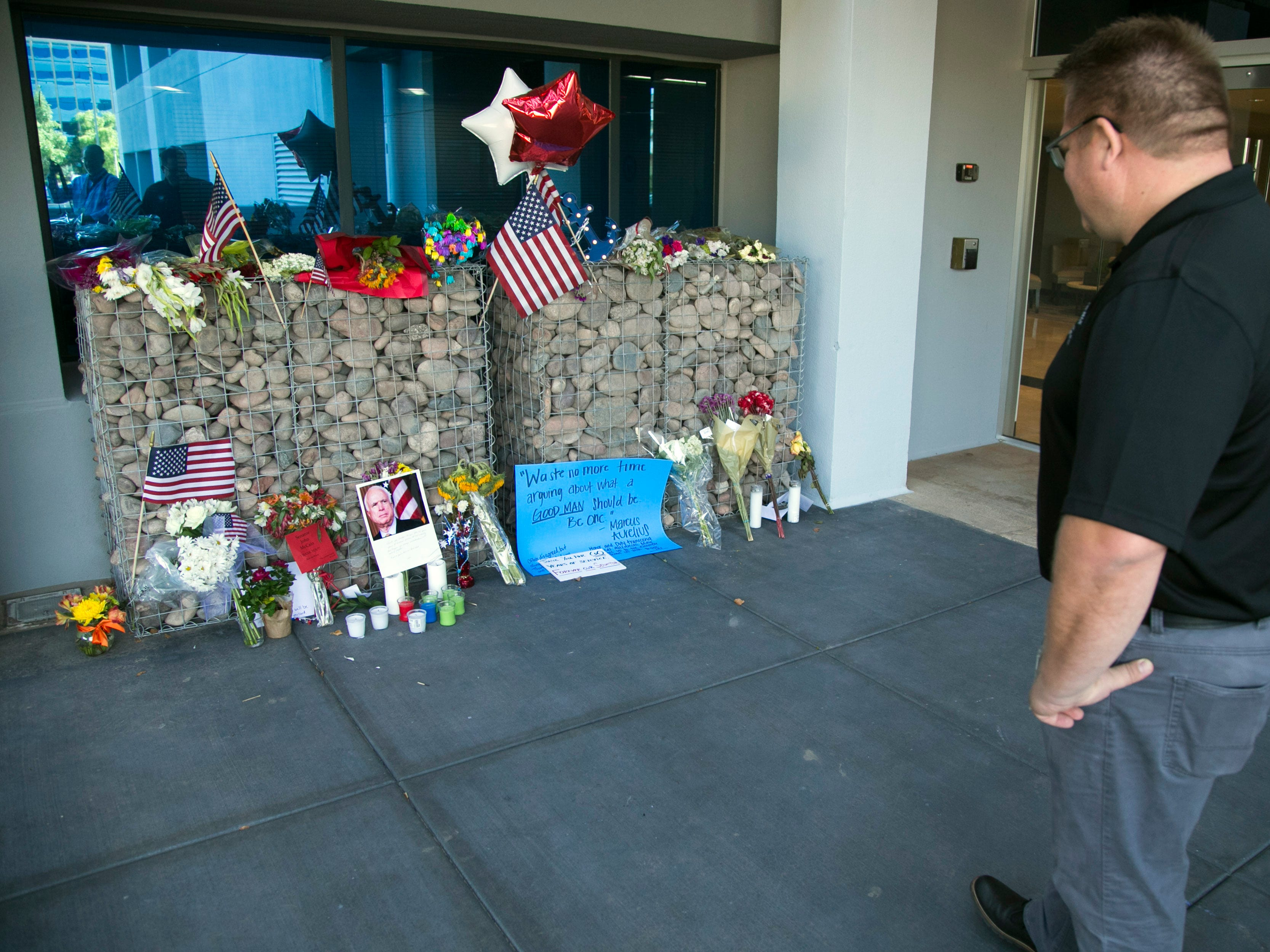 Ted Olsen of Phoenix looks at a memorial for Sen. John McCain at McCain's office in Phoenix on Aug. 27, 2018.