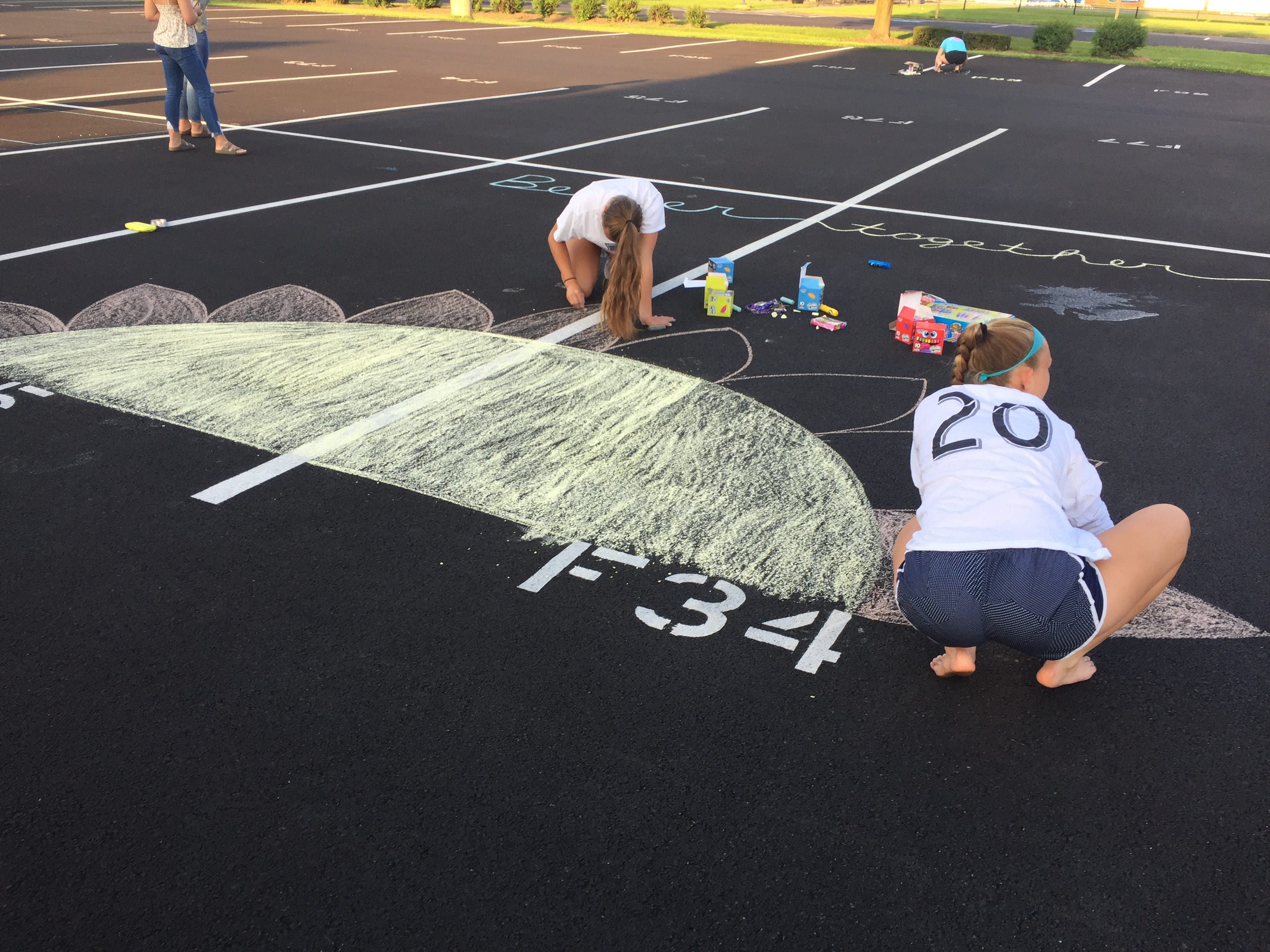 Cedar Crest High School seniors took out the chalk and decorated their parking spots on Saturday evening in preparation for the new school year. This is the second year, seniors have decorated their parking spots. Here, Sam Gerhart and Sydney Snyder work on their parking spots.