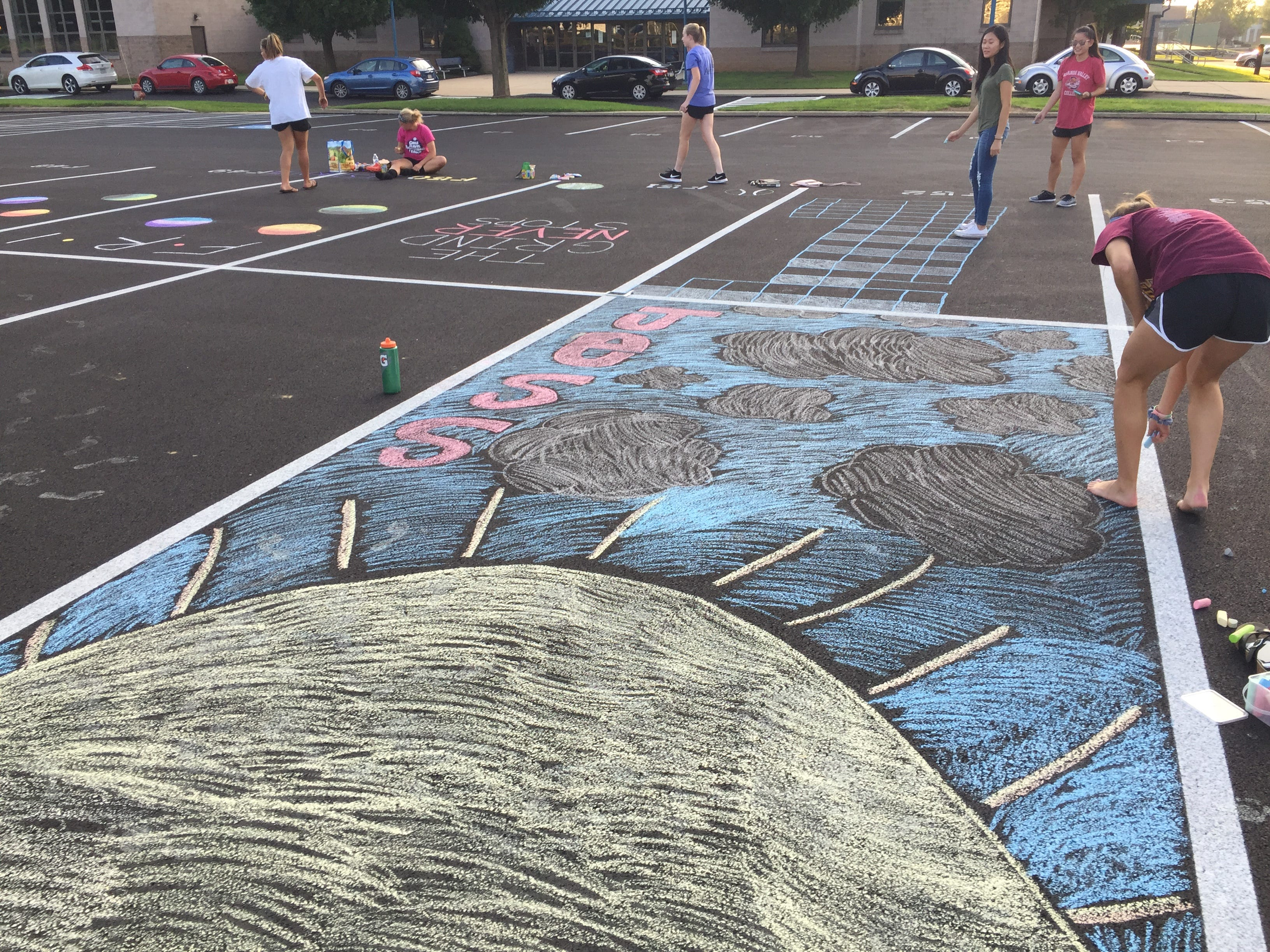 Cedar Crest High School seniors took out the chalk and decorated their parking spots on Saturday evening in preparation for the new school year. This is the second year, seniors have  decorated their parking spots. Here, senior Jess Emrich puts the finishing touches on her spot.