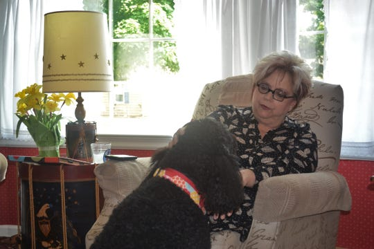 Rebecca Booth enjoys a quiet moment with her dog, Tigger, in her Genoa home. Booth will host her annual art open house at the home on Dec. 8 and 9.