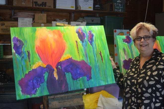 Artist and businesswoman Rebecca Booth stands in her Genoa garage with the iris painting she created in her unique impressionist style.
