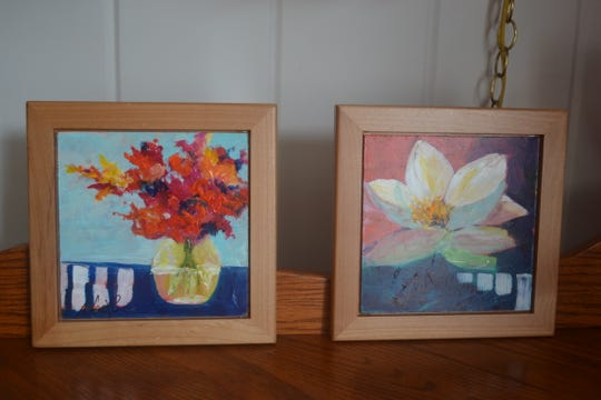 """Booth usually paints this small tile """"mini paintings"""" of flowers in vases and flowers growing wild. Several of her paintings, along with her unique jewelry, will be available for sale at her December open house."""