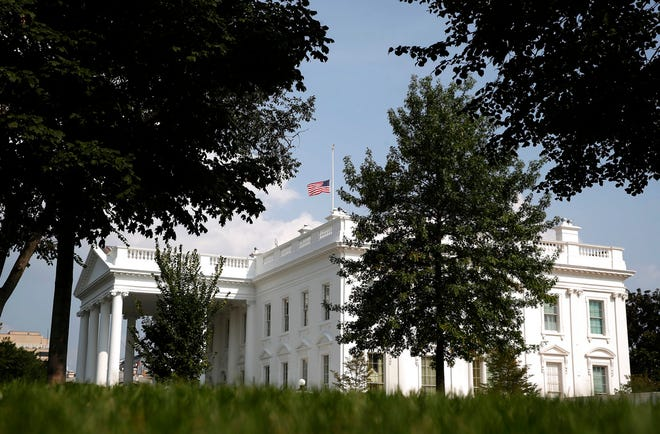 """The American flag files at half-staff at the White House, Monday afternoon, Aug. 27, 2018, in Washington. Two days after Sen. John McCain's death, President Donald Trump says he respects the senator's """"service to our country"""" and has signed a proclamation to fly the U.S. flag at half-staff until his burial. The flag atop the White House flew at half-staff over the weekend but was raised Monday and then lowered again amid criticism. (AP Photo/Alex Brandon)"""