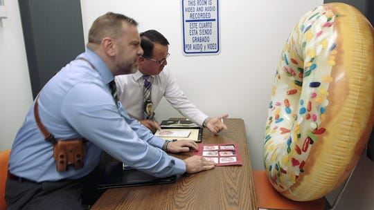 """York City Police Detectives George Ripley, foreground, and Andy Baez, background, interrogate a large doughnut in the police lip-sync video that was pulled from being shown at the York Revolution game on Saturday. York Mayor Michael Helfrich called Maple Donuts, featured in the video, a company  that uses """"divisive messaging"""" in its ads."""