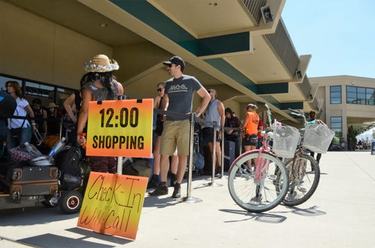 Burners wait outside the north end of the Reno-Tahoe International Airport for buses to take them to Black Rock City.