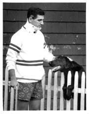 Geoff Mandile pets his dog Jarvis after returning home to recover from a neck injury in 1989.