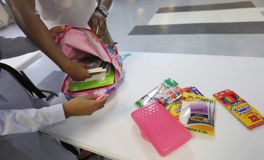 Volunteers pack supplies into backpacks Saturday at Barakah Muslim Charity on Jefferson Avenue.