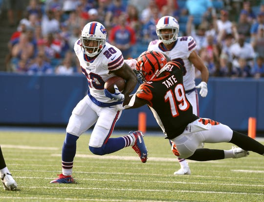 Bills safety Rafael Bush slips past Bengals Auden Tate after intercepting a tipped pass.