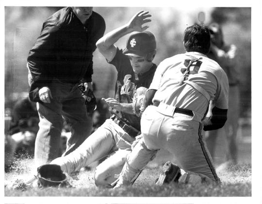 Geoff Mandile of Ithaca College slides under RIT catcher Rob Hrankowski during the first game of a doubleheader on April 25, 1991. Mandile, who broke his neck playing in a junior varsity football game in 1989, returned to the diamond about 14 months later. He is now the varsity football coach at Victor High School.