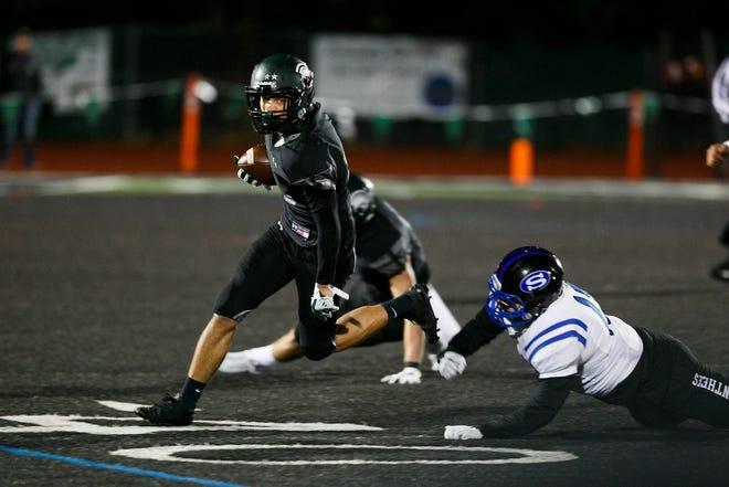 West Salem's Anthony Gould (15) dodges a tackle in an OSAA 6A quarterfinal game against South Medford on Friday, Nov. 17, 2017, at West Salem High School.